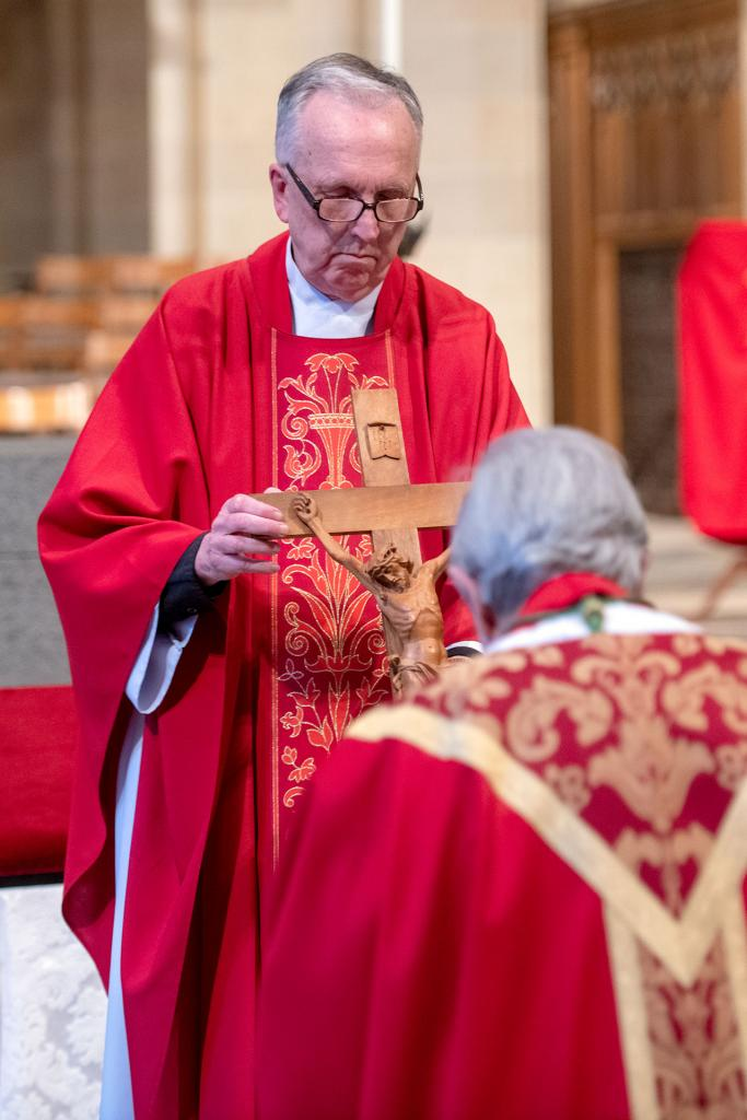 Father Kevin McKenna holds the cross for Bishop Matano to venerate during the Good Friday service April 10.