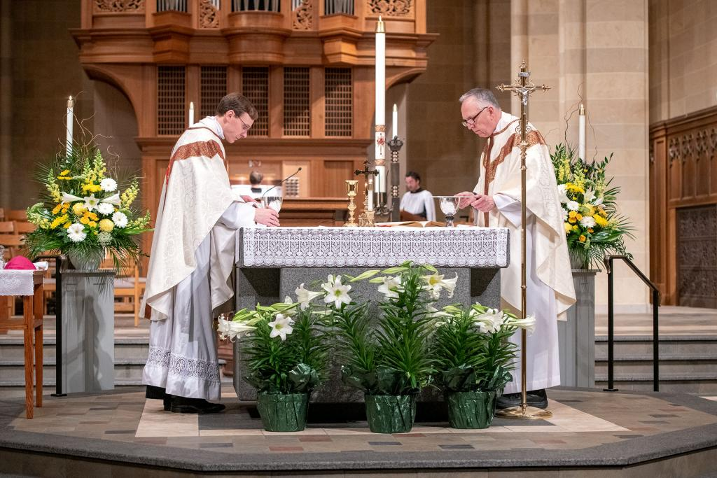 During the livestreamed Easter Vigil April 11, Father Daniel White (right) and Father Kevin McKenna practice social distancing while celebrating the Eucharist.