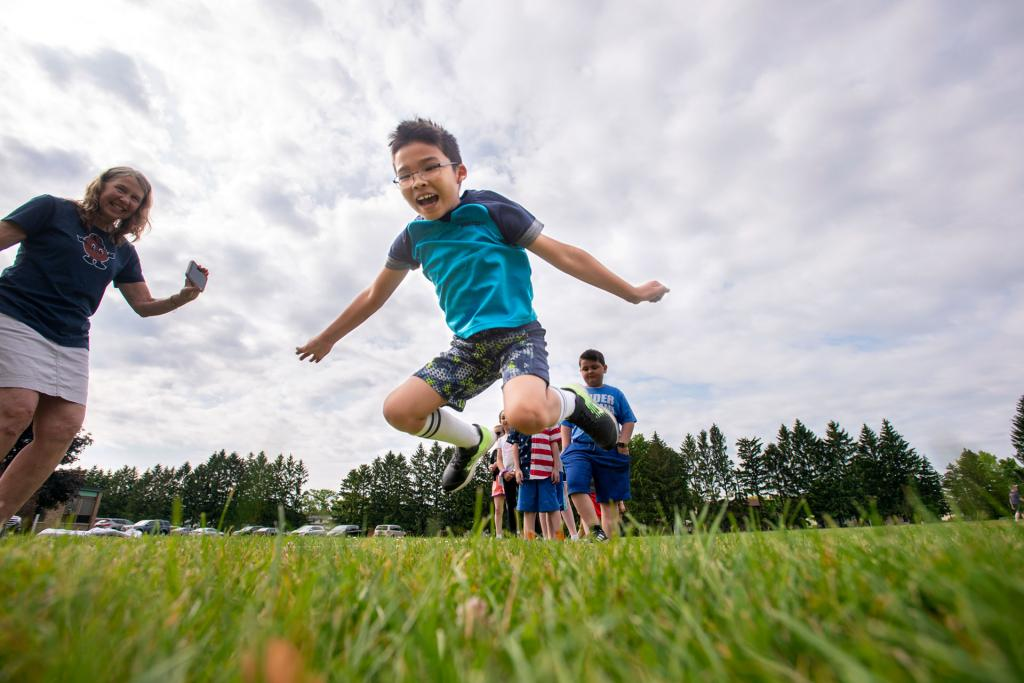 Second-grader Caleb Vanphila sees how far he can jump during a field day activity June 18 at Irondequoit's St. Kateri School. (Courier photo by Jeff Witherow)