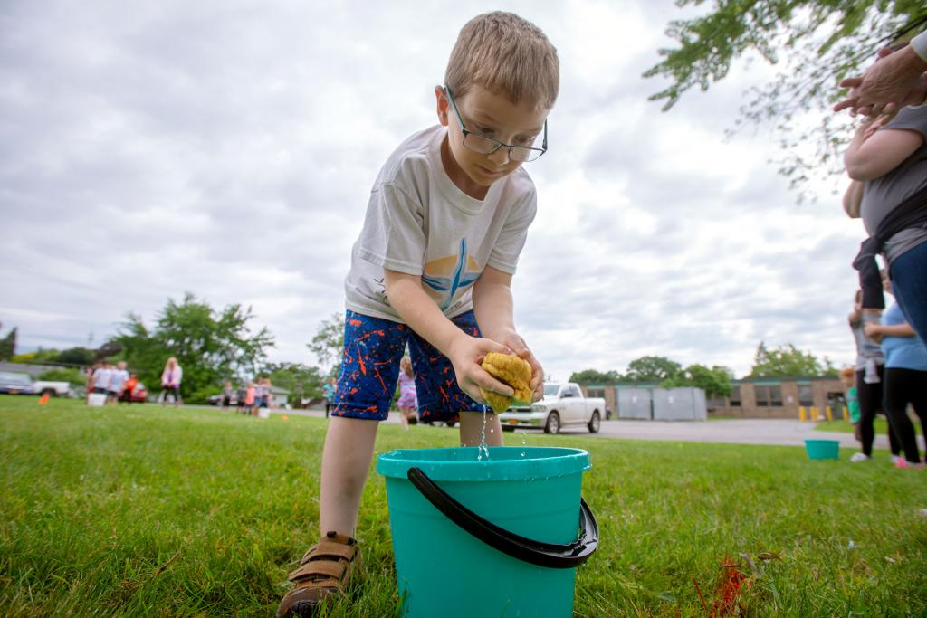 Kindergartner Vinny Trevisani squeezes out a sponge during a field day activity at Irondequoit's St. Kateri School June 18. (Courier photo by Jeff Witherow)