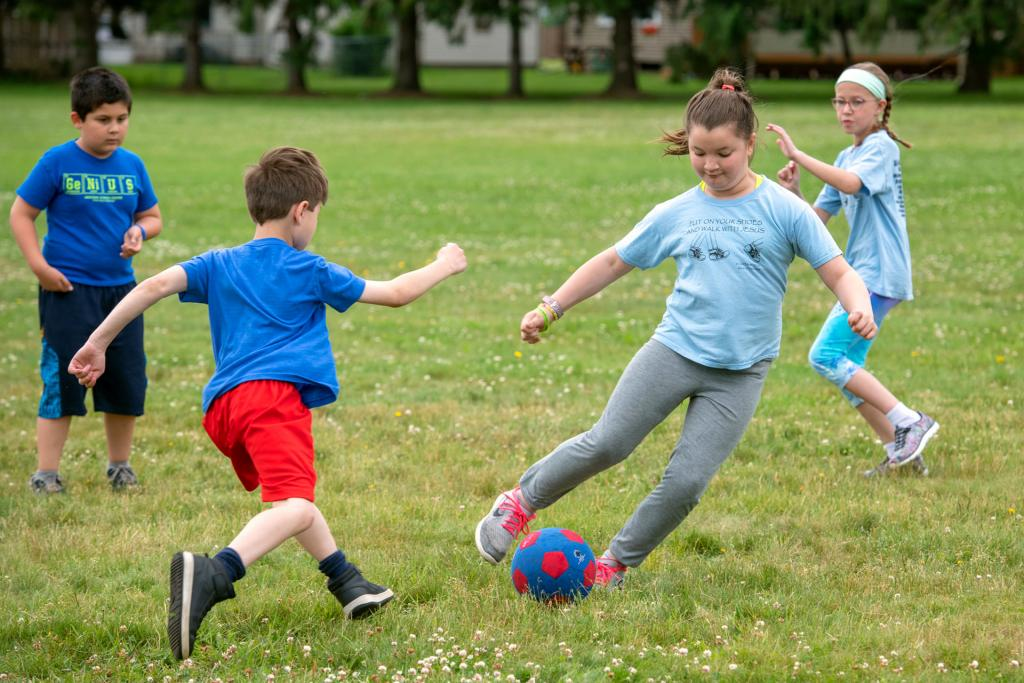 Third-graders John Georges (from left), Tomas Budi, Addie Sinesiou and Lauren Caroll play a game of soccer during the field day activities at St. Kateri School in Irondequoit June 18. (Courier photo by Jeff Witherow)