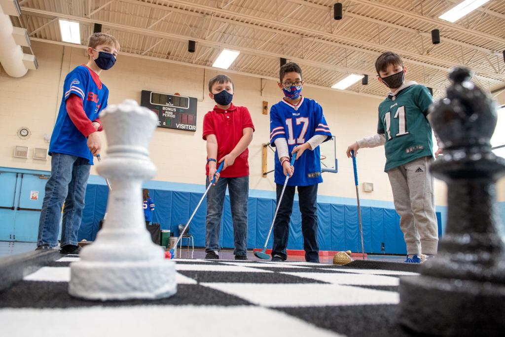 Barrett Condon (from left), Andrew Norris, Gabriel Napolitano and Anthony Avila play miniature golf in the gym at St. Lawrence School in Greece.