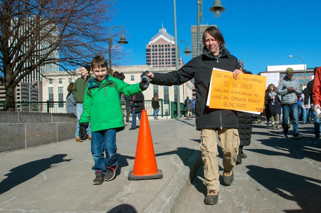 Theo and Doug Keener walk hand in hand down Court Street.