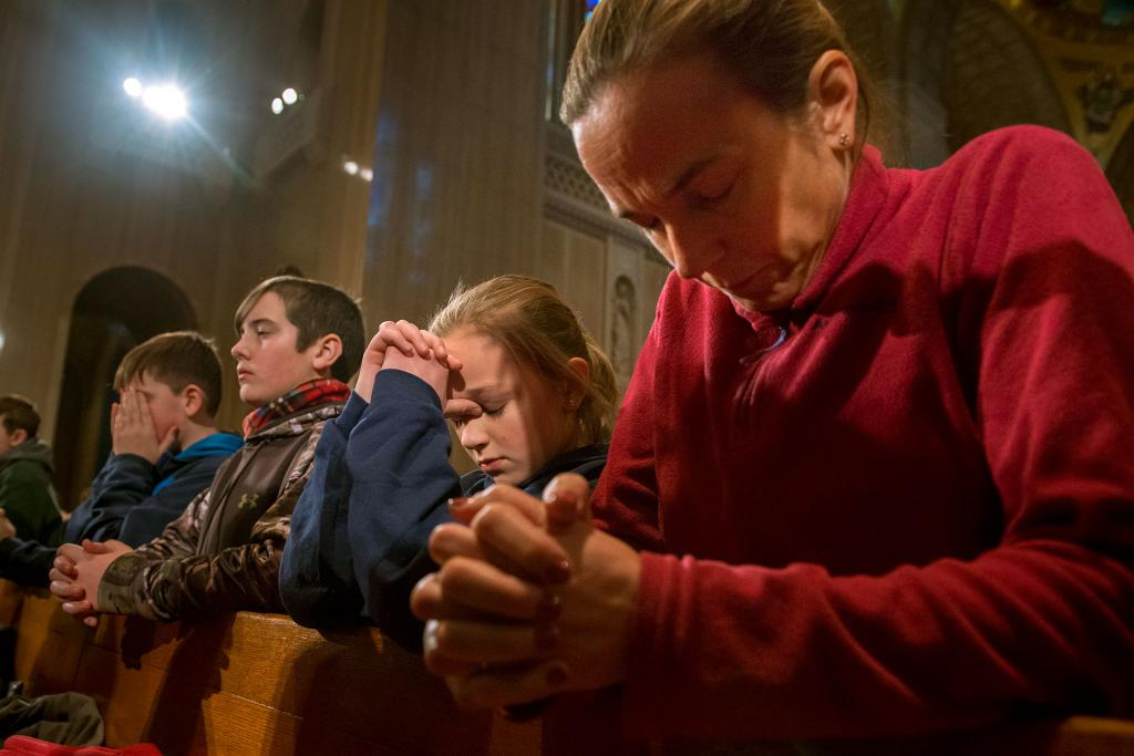 Eleven-year-old Sarah Lawson of Addison (left) and her mother, Julie Lawson (right), kneel during Mass.