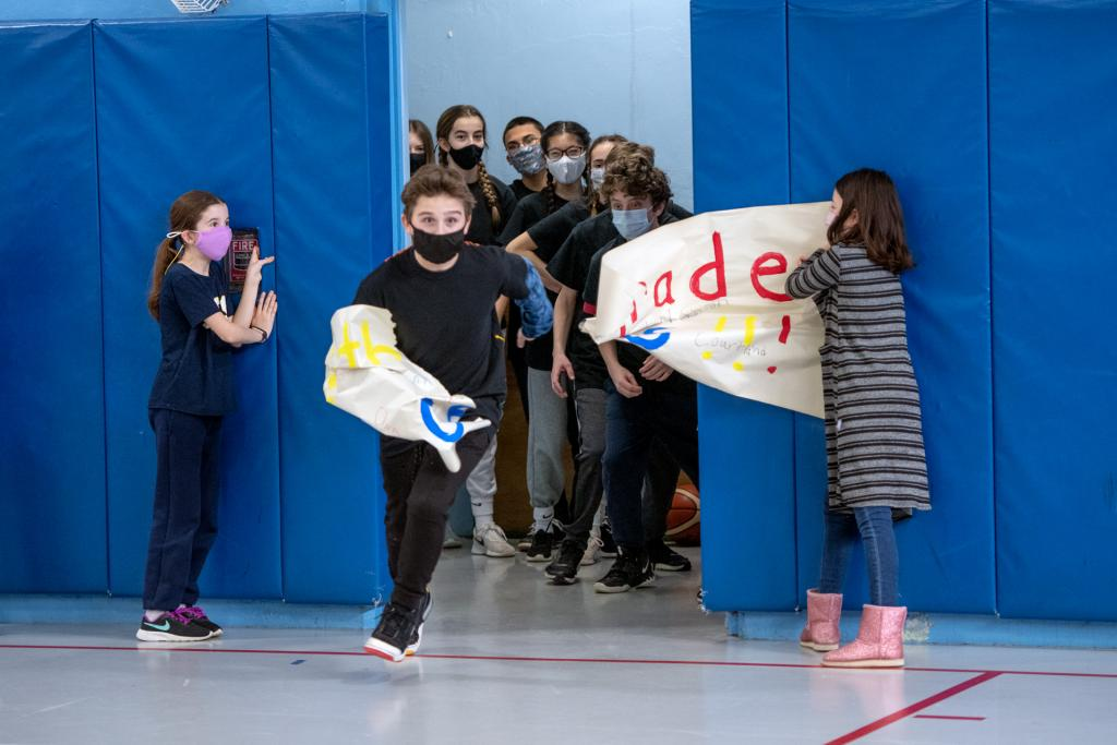 Members of one of St. Mary School's volleyball teams break through a sign at the start of the game.