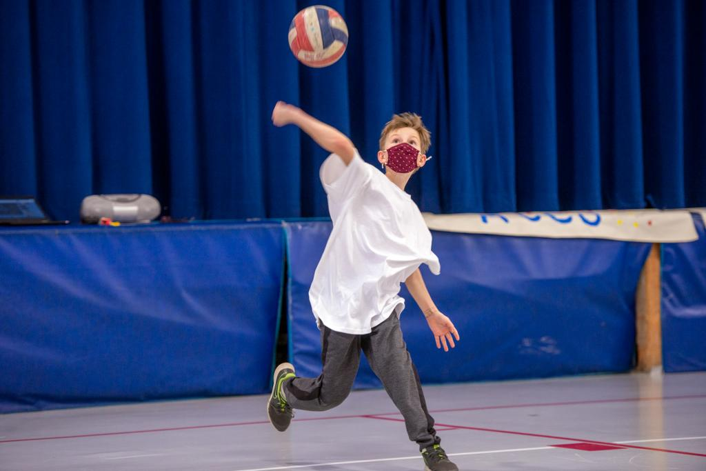 Sixth-grader Henry May serves the ball during the game.