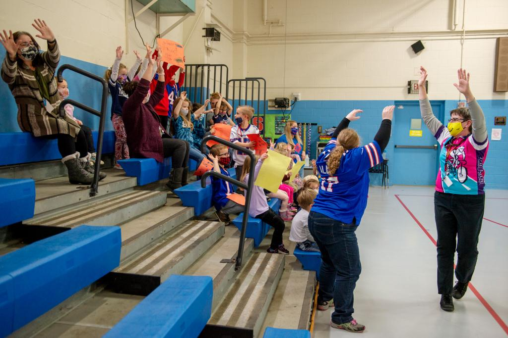 Sister Laurie Orman has students do the wave during the volleyball game.