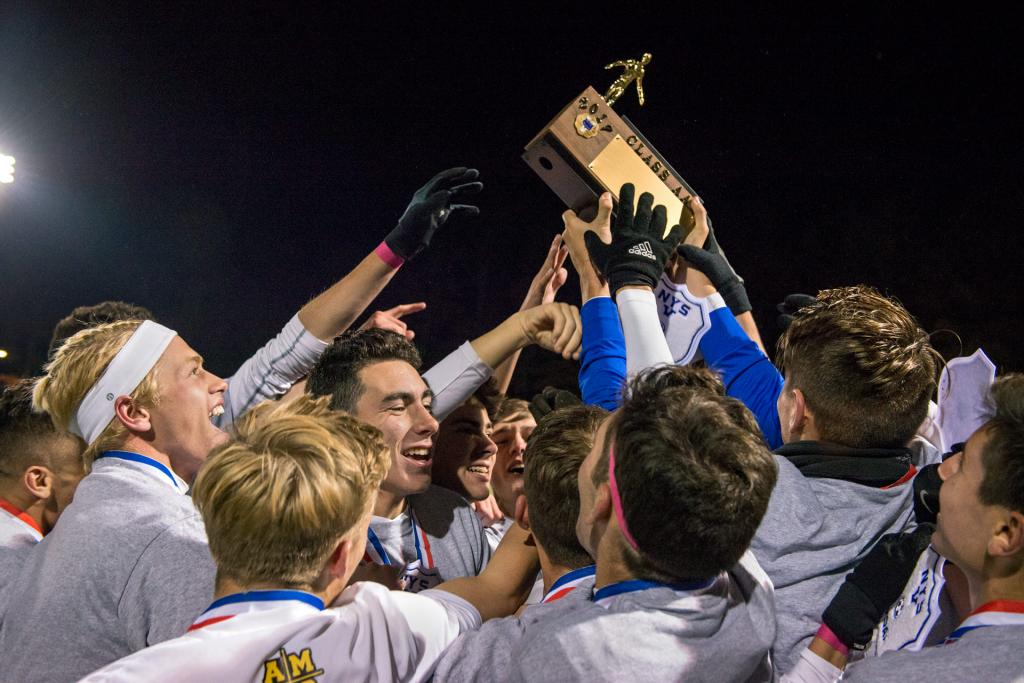 Members of the McQuaid soccer team reach for the Section 5 championship trophy after their 2-1 win against Hilton in the Section 5 Class AA championship game Oct. 31.