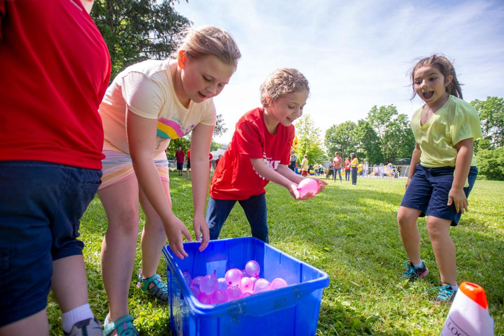 Meggie Pratt (from left), Lakelyn Lewis and Nora Murphy grab water balloons during the St. Michael School field day in Penn Yan June 17. (Courier photo by Jeff Witherow)