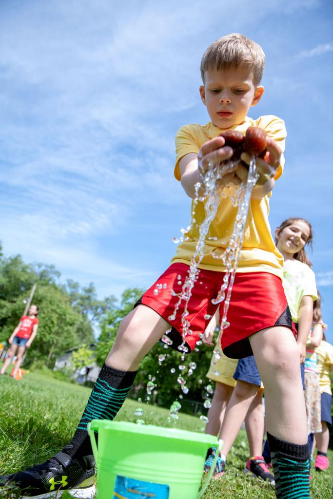 Caleb Fisher wets a sponge during a field day outdoor game at St. Michael School in Penn Yan June 17. (Courier photo by Jeff Witherow)
