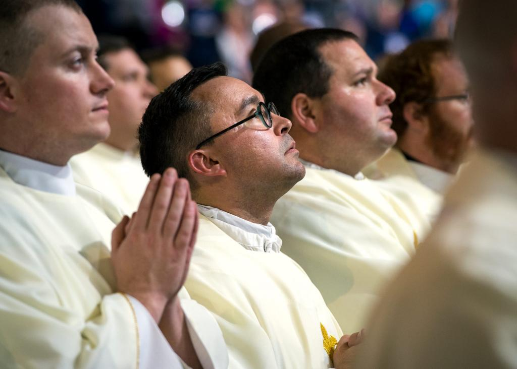 Father Matthew Jones looks up at the display monitors following the procession into Mass at Lucas Oil Stadium Nov. 18.