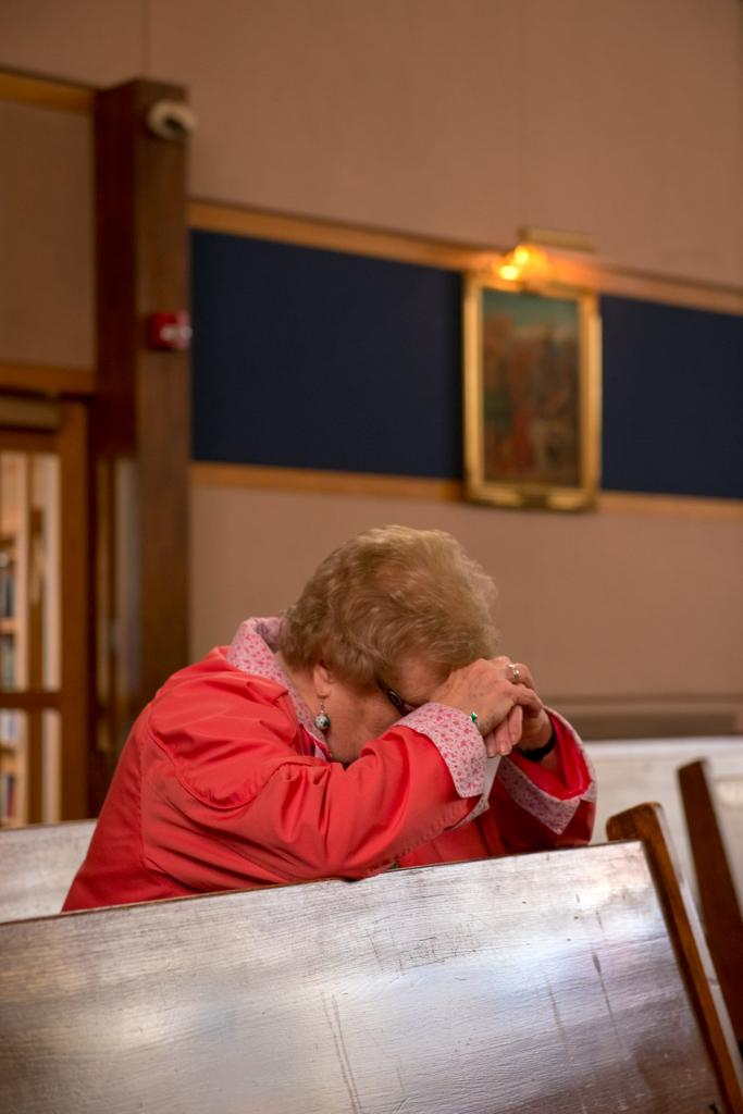 Louise Salva bows her head in prayer at Our Mother of Sorrows Church in Greece March 13 during the Day of Penance and Mercy.