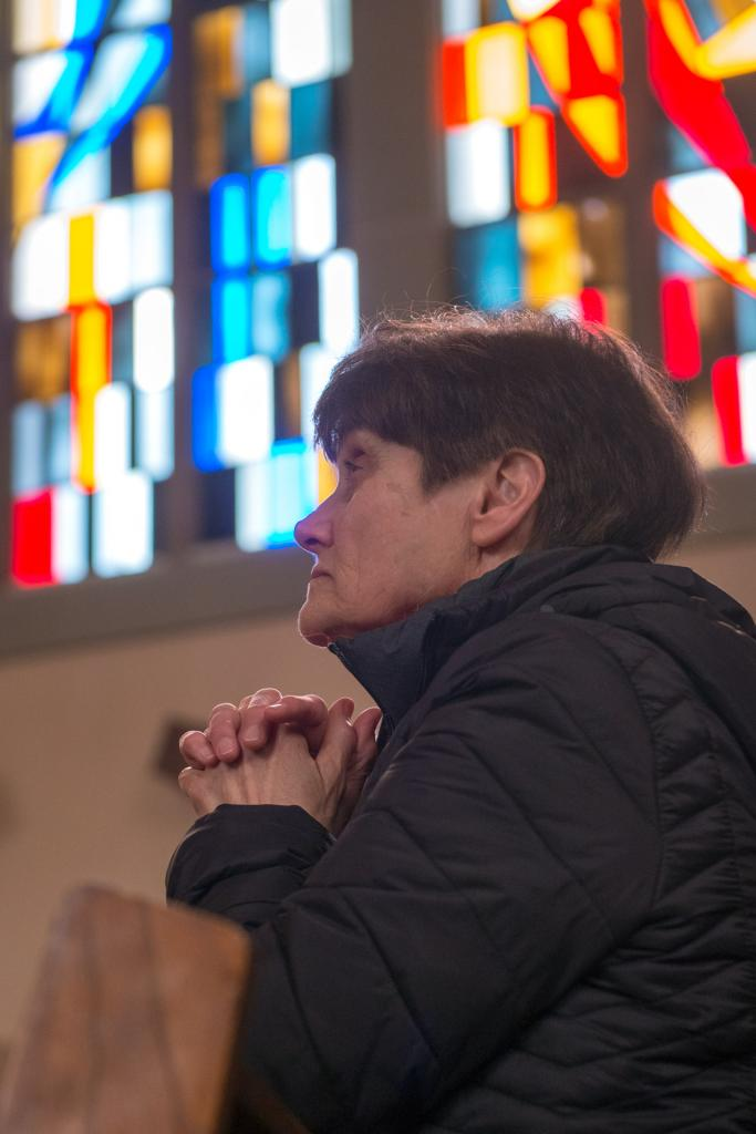 Jan Gallucci kneels in prayer at Our Mother of Sorrows Church in Greece.