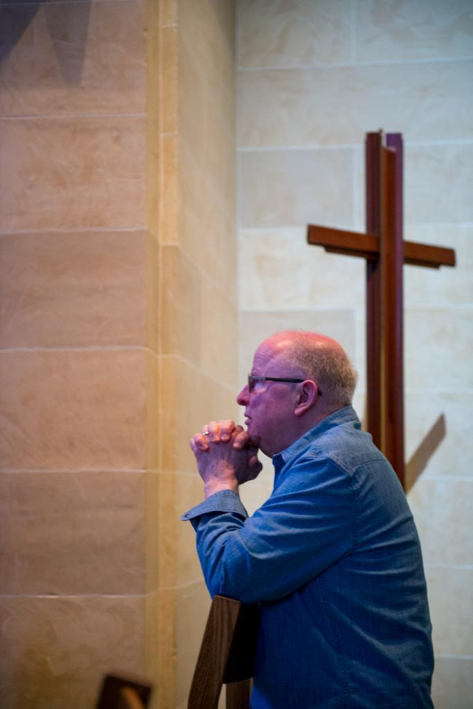 Rich Bidwell kneels before the Blessed Sacrament at Rochester's Sacred Heart Cathedral.