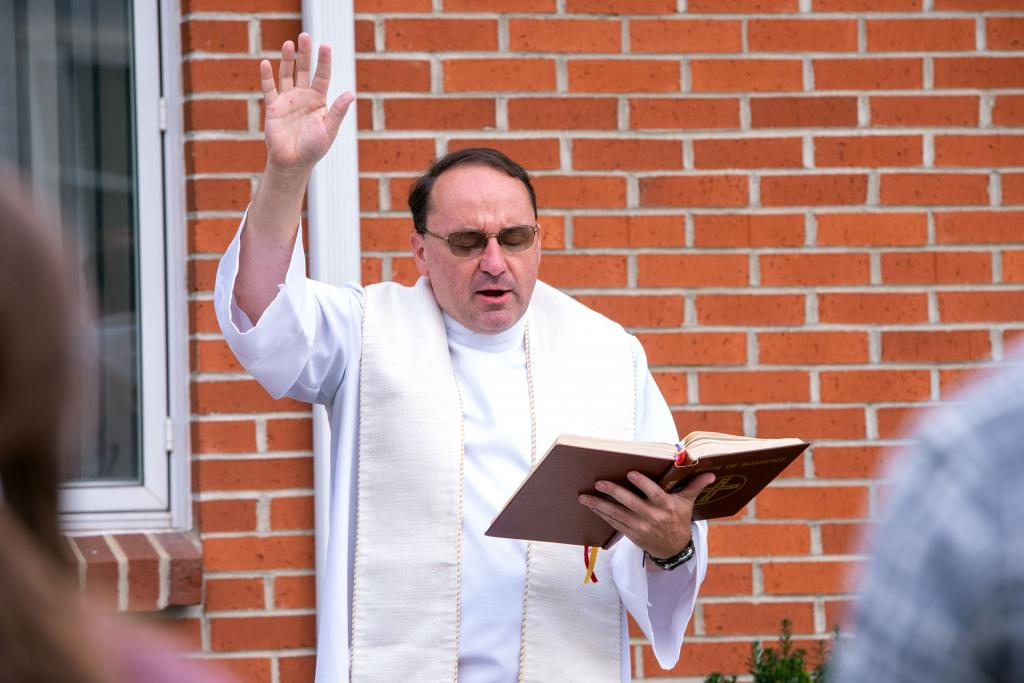 Father Jeffrey Tunnicliff raises his hand to bless the animals.