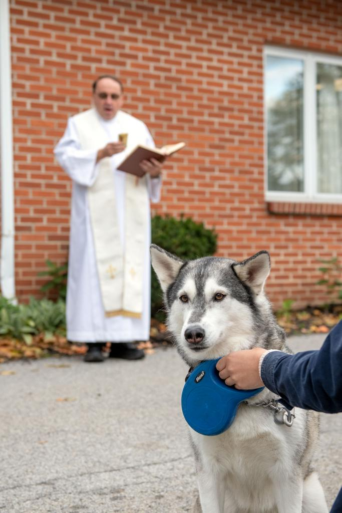 Katharina Nieves holds onto her dog Juneau during the blessing.