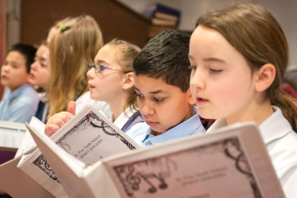 St. Pius Tenth School students sing in the choir before Mass. (Courier photo by Jeff Witherow)