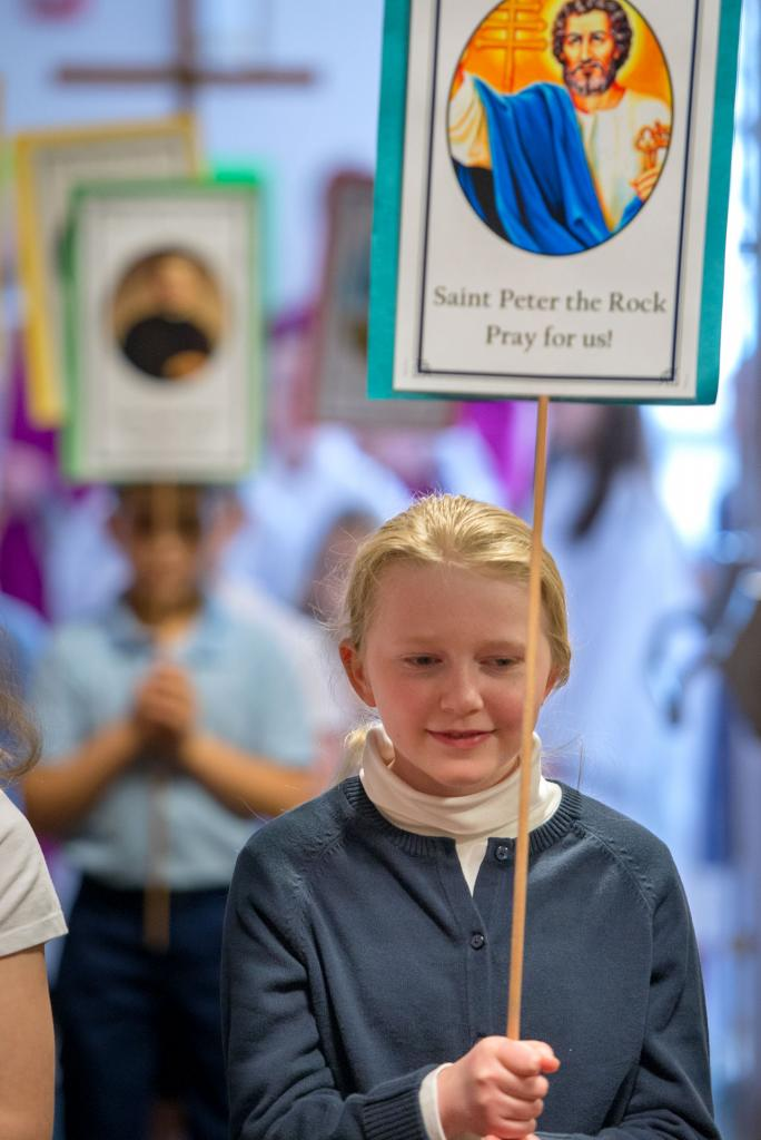 St. Pius Tenth School fourth-grader Elizabeth Michaels processes into Mass. (Courier photo by Jeff Witherow)