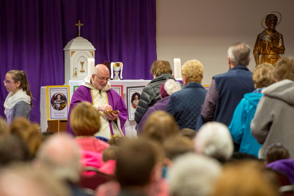 Father Paul Bonacci distributes Communion. (Courier photo by Jeff Witherow)
