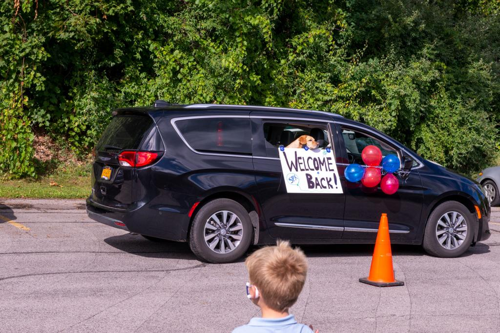 Parents drive by the school to welcome students back to class.
