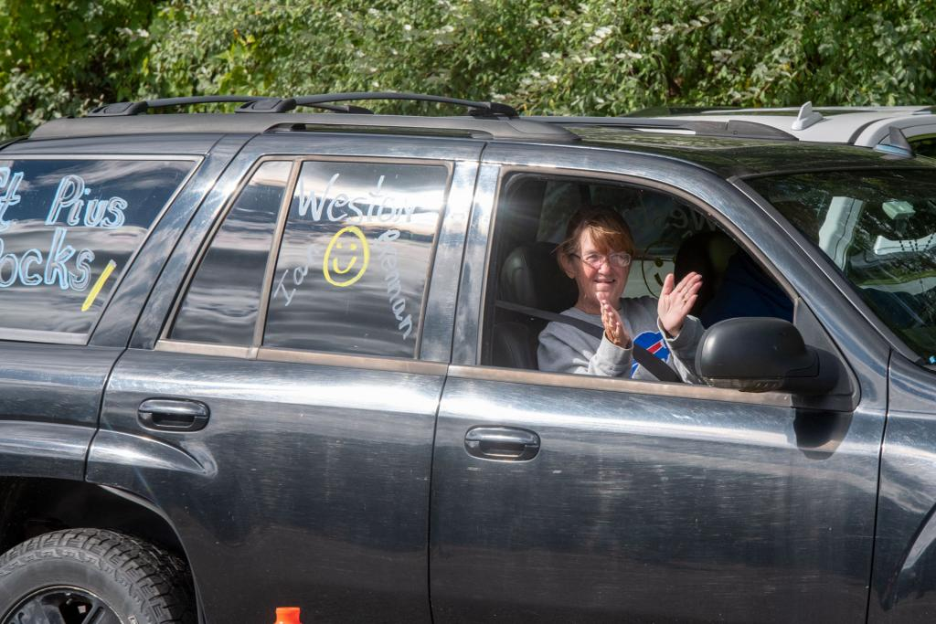 A parent participating in the parade waves to students.