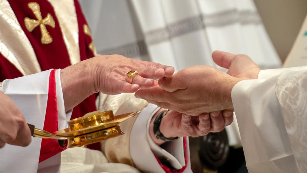 Bishop Matano anoints Father Chichester's hands.