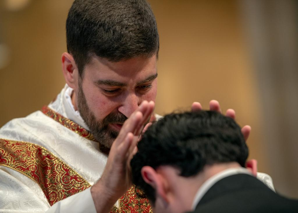 Father Jeffrey Chichester gives a blessing to Father Anthony Amato.