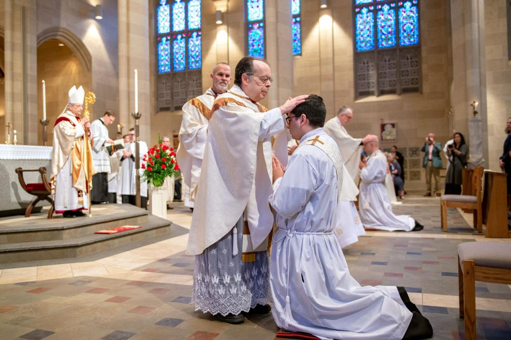 Father Ronald Antinarelli lays his hands on the head of Father White.