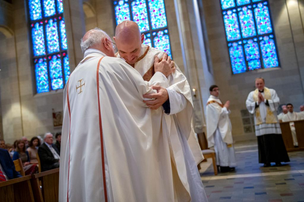 Father Walter is vested by Father Dennis Bonsignore.