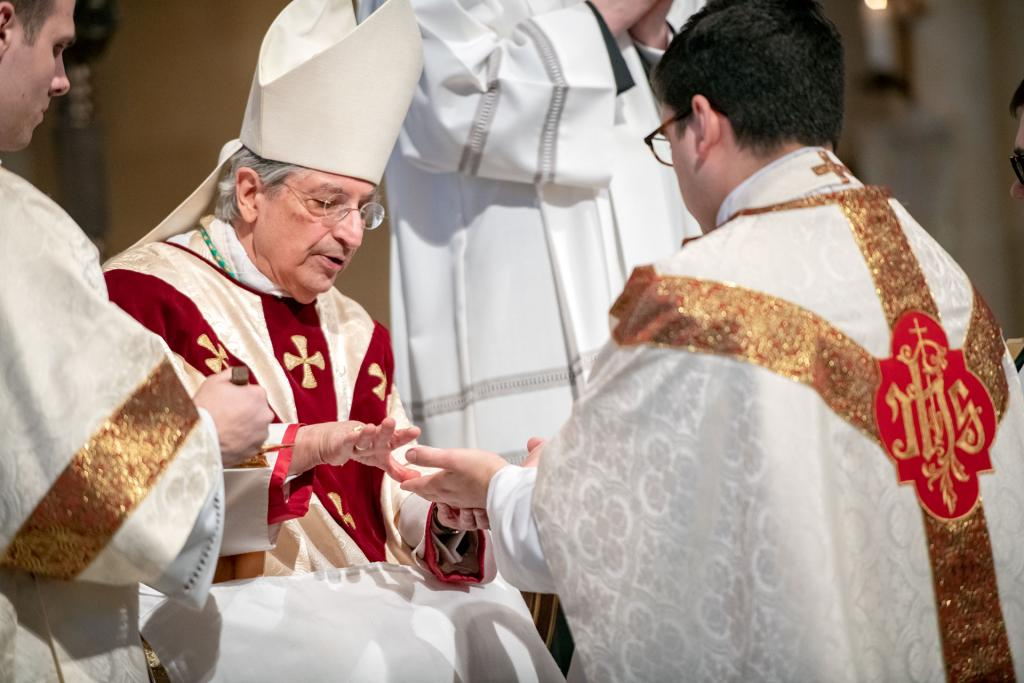 Bishop Matano anoints the hands of Father White.