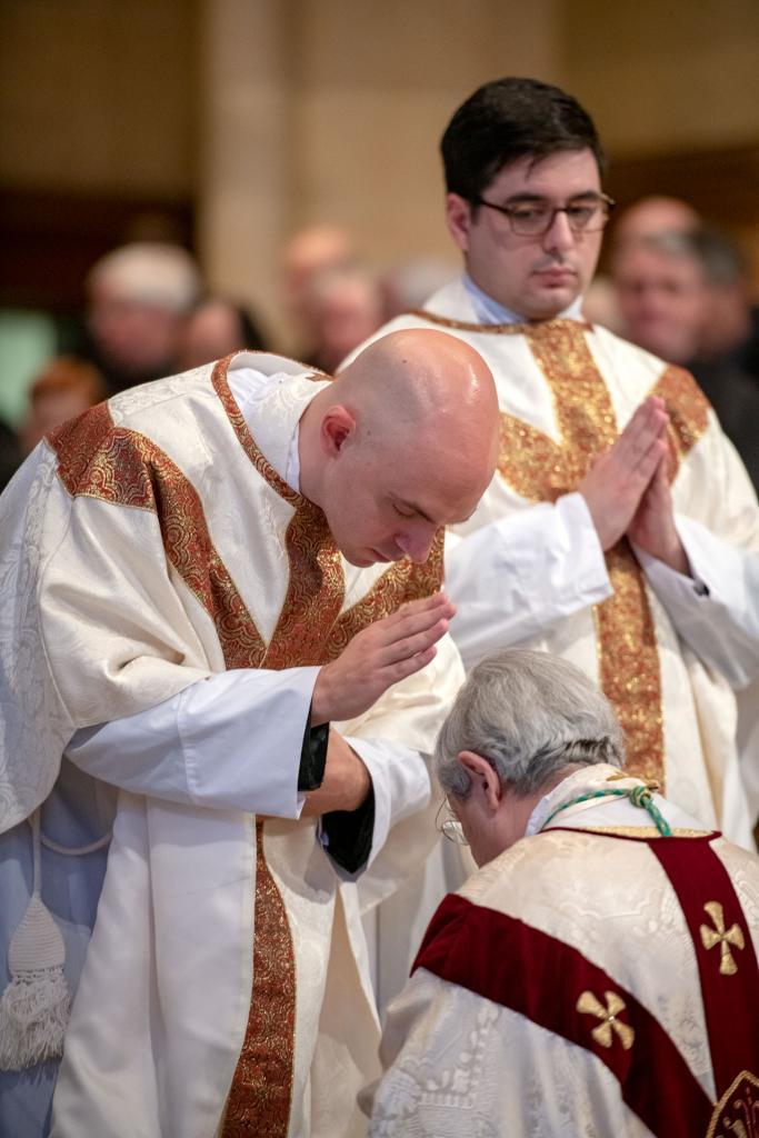 Bishop Matano receives a blessing from Father Walter at the conclusion of the Mass.