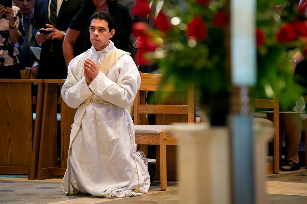 Father Anthony Amato kneels before prostrating.
