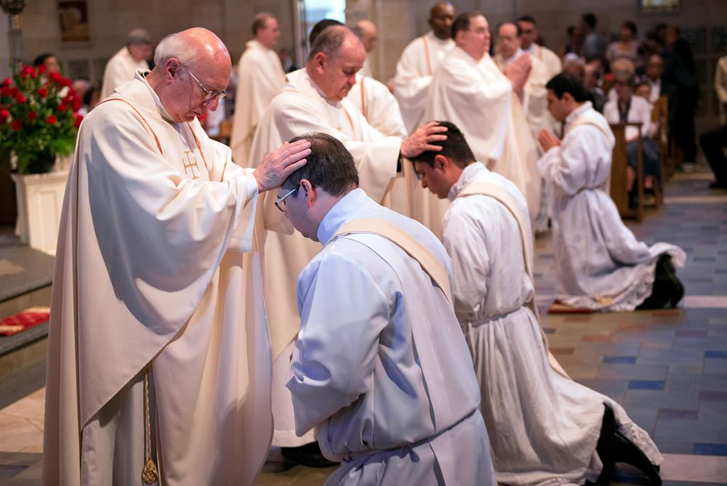 Diocesan priests line up to lay their hands on the heads of the newly ordained priests.