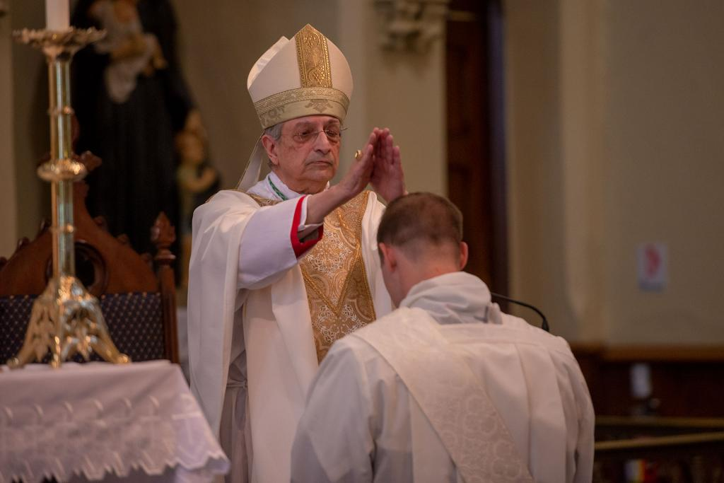 Bishop Matano lays his hands on the head of Father Martuscello.