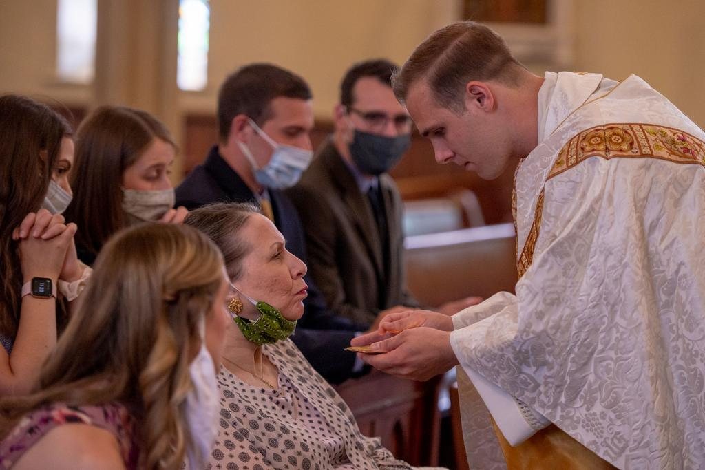 Father Martuscello gives communion to his mother.
