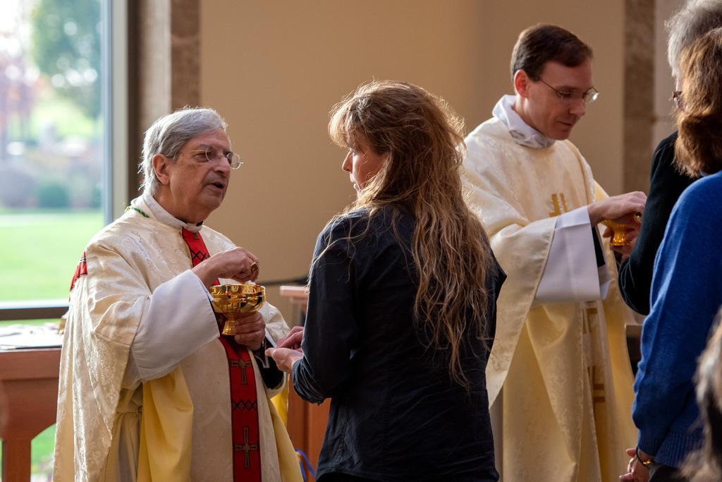 Bishop Matano and Father Daniel White distribute Communion.