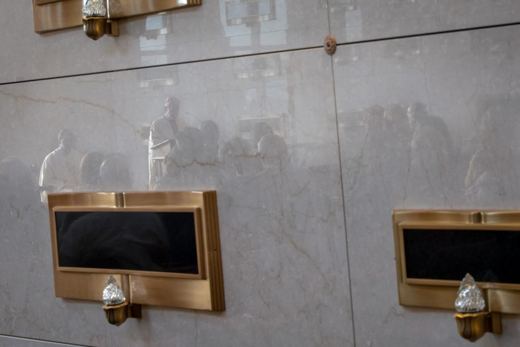 Bishop Matano is reflected in the mausoleum's crypts.