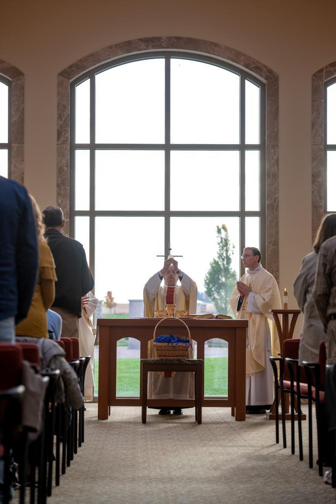 Bishop Matano elevates the Eucharist.