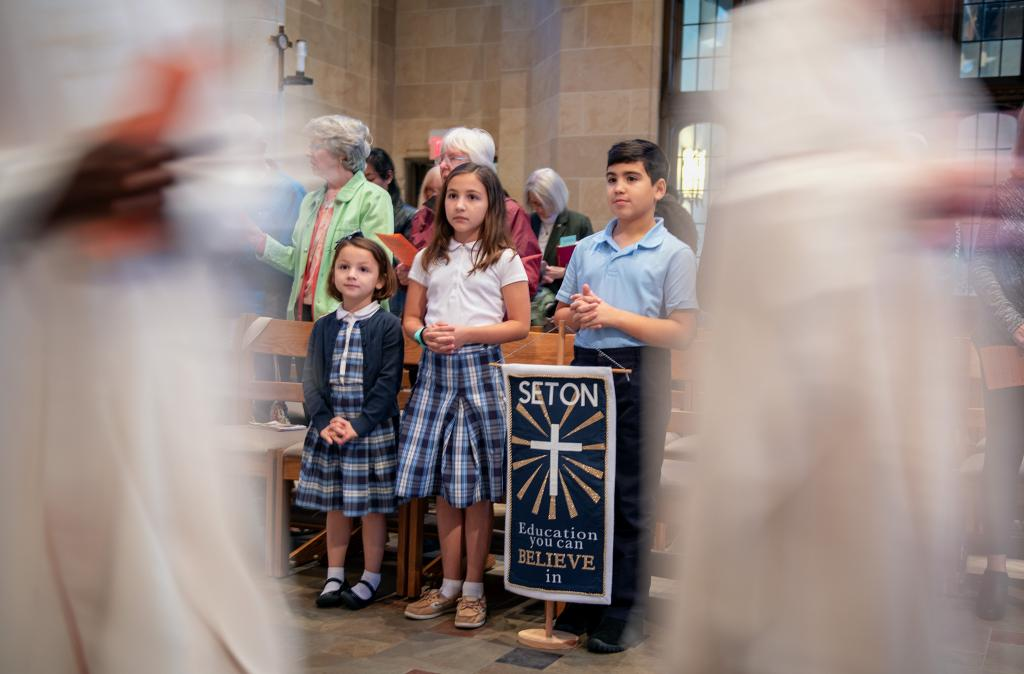 Seton Catholic School students Julia Fleming (from left,) Josie Fleming and Marco DeAscentiis watch the procession during the annual Respect Life Mass Oct. 6 at Rochester's Sacred Heart Cathedral.