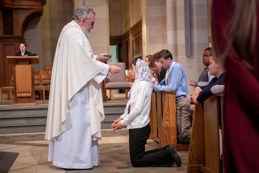 Tamara Gueste receives Communion from Father Daniel Condon.