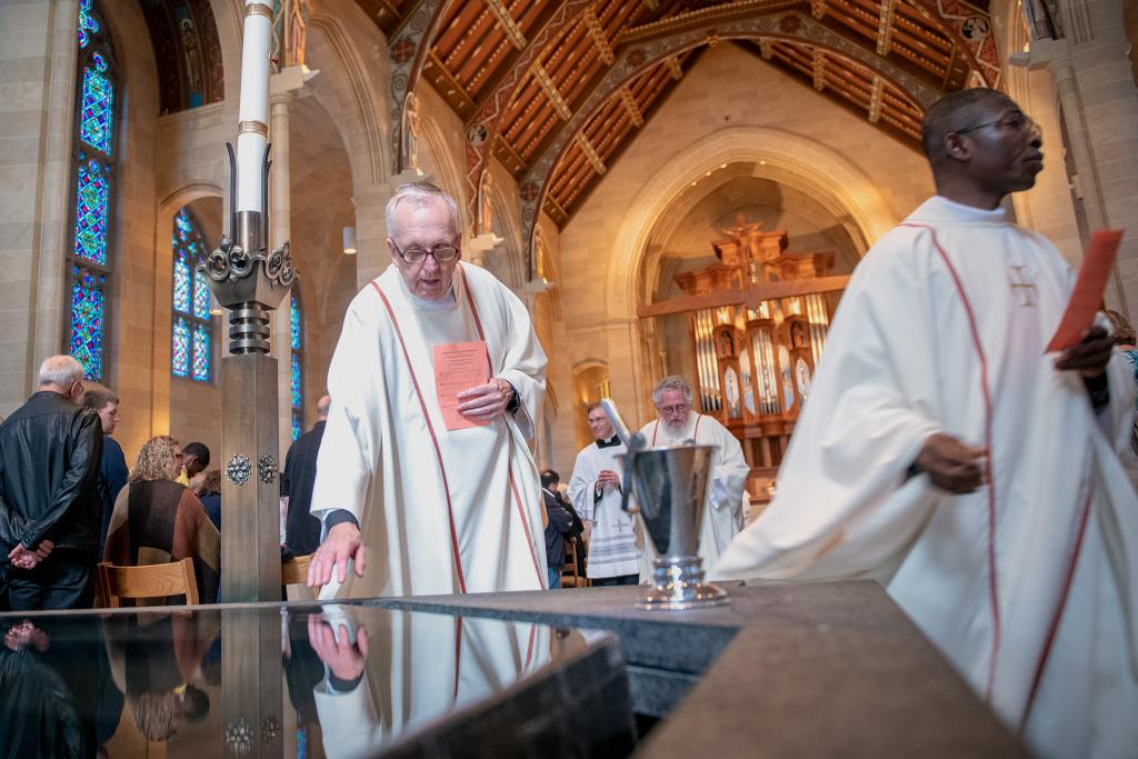 Father Kevin McKenna blesses himself with holy water during the recession from Mass.