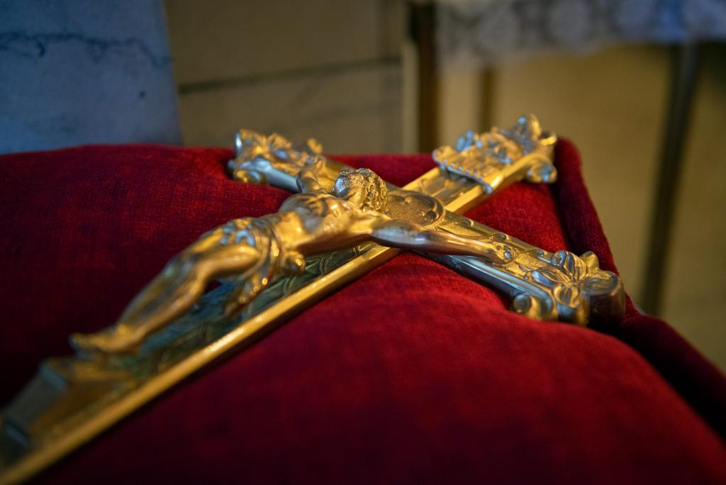 A crucifix rests on a pillow.