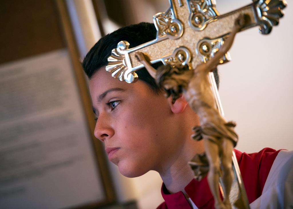 Altar server Sean Geen waits to process into Mass.