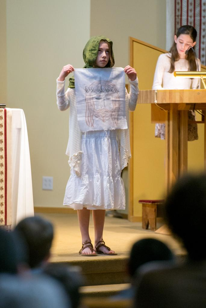 Veronica, played by Kennedy Spencer, displays the cloth used to wipe the face of Jesus.