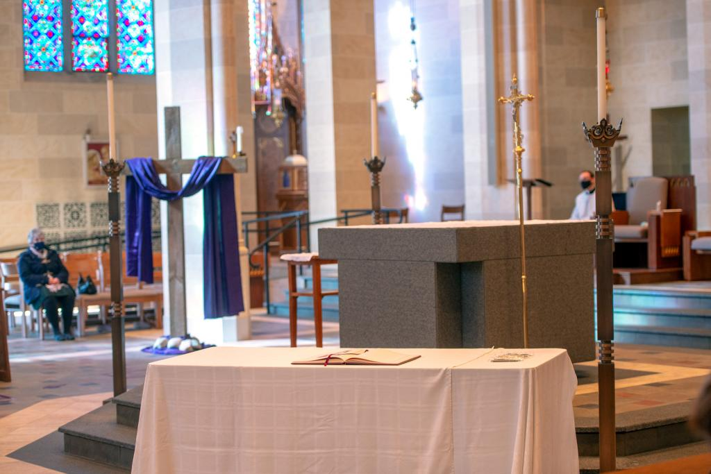 A large wooden cross and the Book of the Elect are seen near the altar at Rochester's Sacred Heart Cathedral.