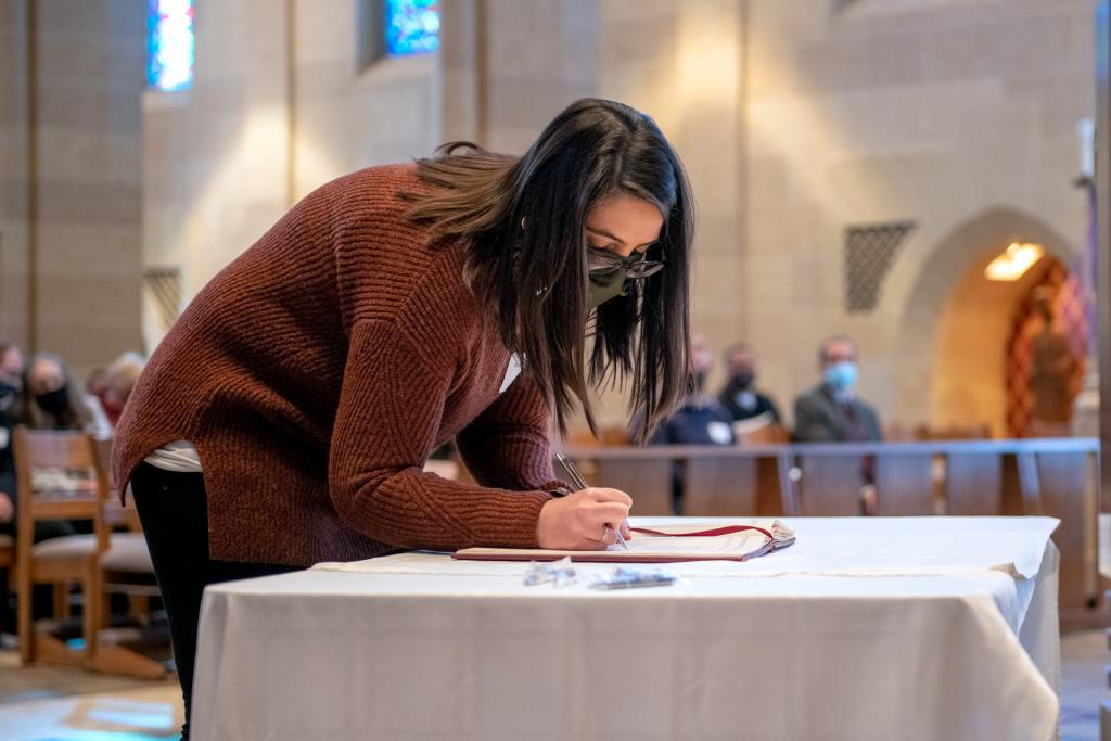 Catechumen Christina Ashbery signs the Book of the Elect.