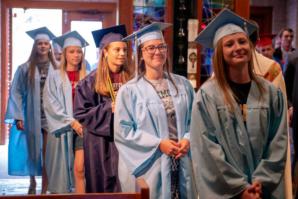 Former students process into the church dressed in their caps and gowns.