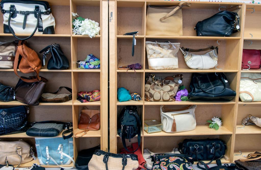 Shelves are filled with designer handbags.