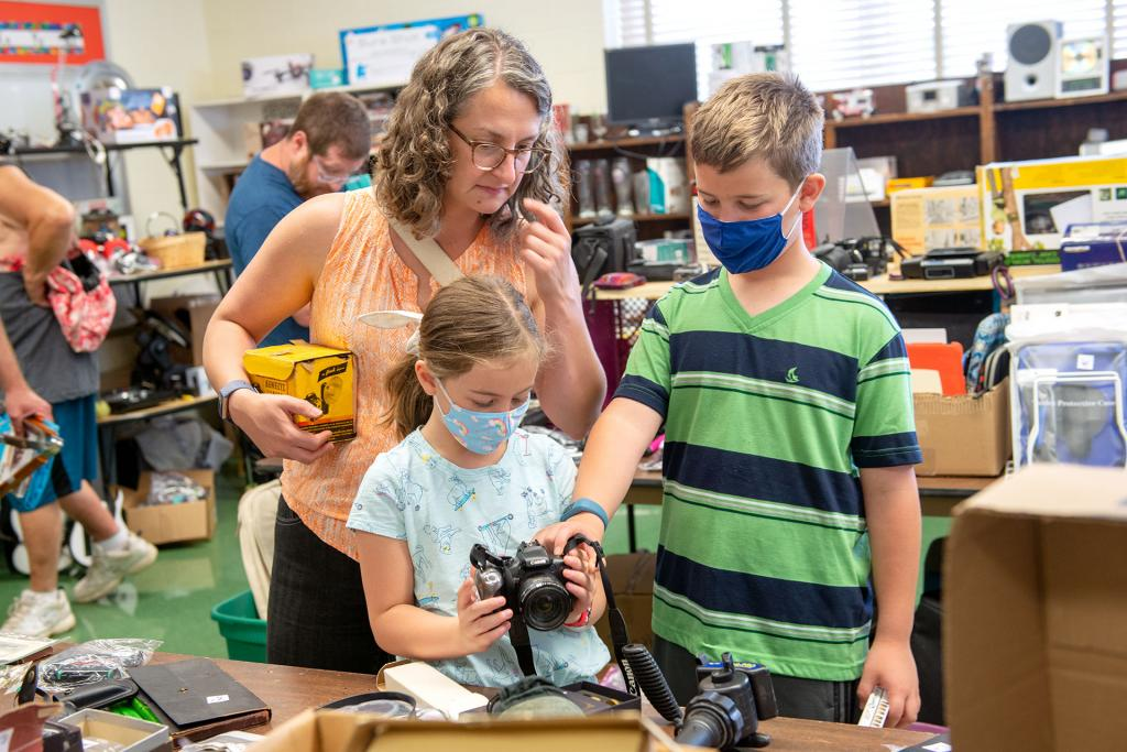 Kara Mucha and her children Hannah and Nathan peruse some used cameras.