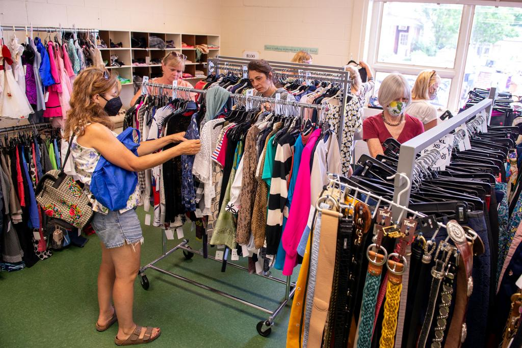 Visitors browse numerous clothing items for sale.